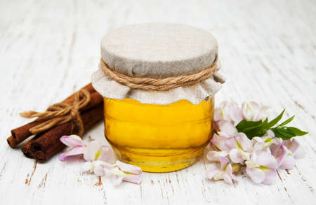 blossom honey: honey with acacia blossoms on a wooden background