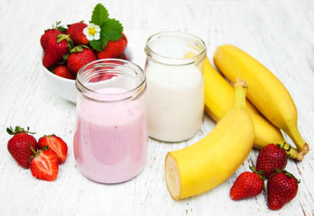 eating banana: Bananas and strawberries with yogurt on a wooden background Stock Photo