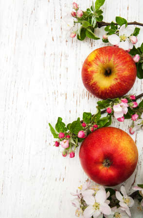 apples and apple tree blossoms on a wooden background