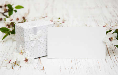 blooming: Spring cherry blossom,  gift box and card on a wooden background Stock Photo