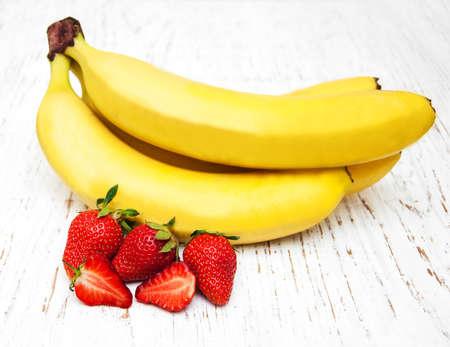 banane: Les bananes et les fraises sur un fond vieux bois Banque d'images