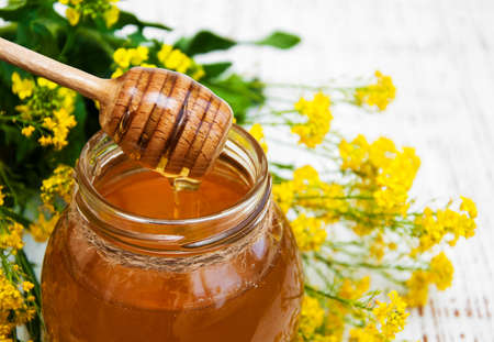 Jar of honey with rape flowers on a wooden background