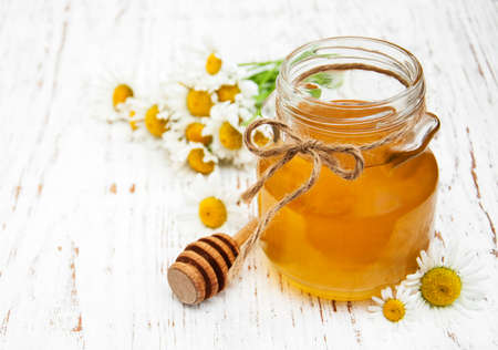blossom honey: Jar of honey with camomile on a old wooden background Stock Photo