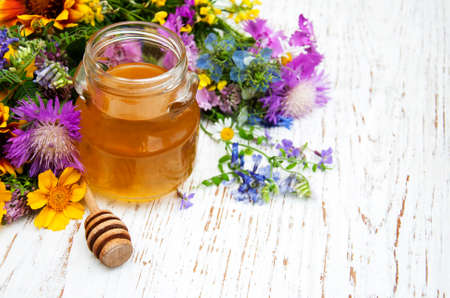 Honey and wild flowers on a wooden background
