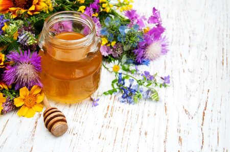 productos naturales: La miel y flores silvestres en un fondo de madera