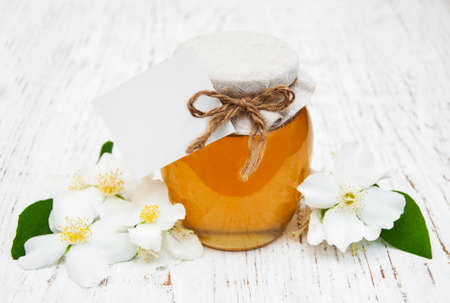 Honey with jasmine flowers on a wooden background