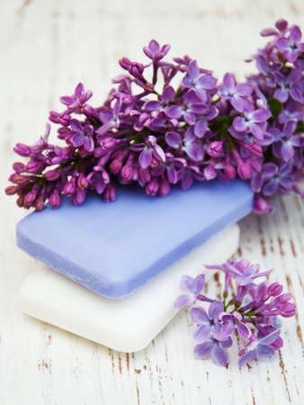 flor violeta: Jabón natural a mano y flores de color lila en un fondo de madera