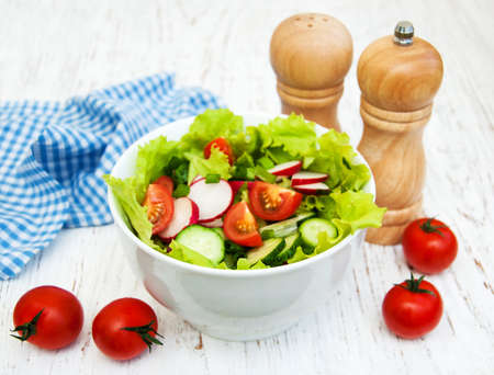 salad bowl: Spring salad with cucumbers and radish on a wooden background Stock Photo