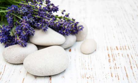 tratamientos corporales: Lavanda y piedras de masaje sobre un fondo de madera vieja