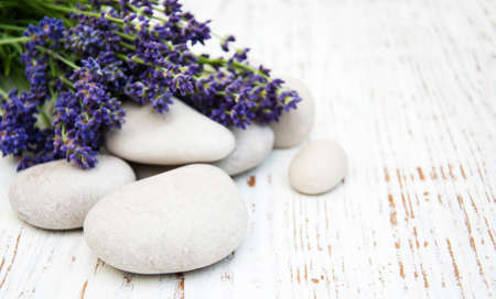 body care: Lavender and massage stones on a old wooden background Stock Photo
