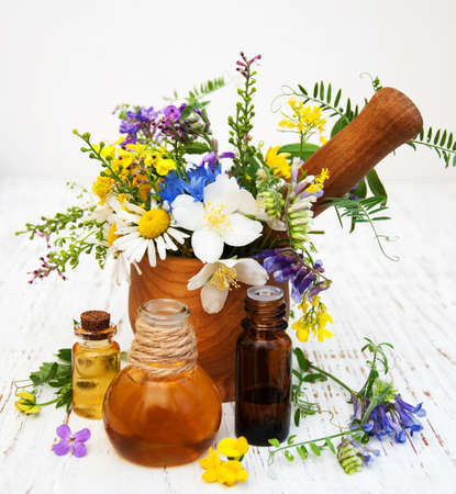 Nature oil with wildflowers on a old wooden background