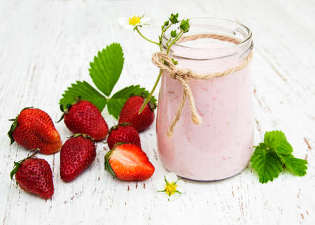 berry smoothie: Strawberry yogurt with fresh strawberries on a wooden background Stock Photo