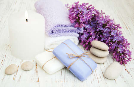 Spa concept - natural soap, towels and lilac flowers