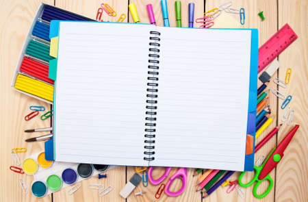 Notebook with school supplies on a wooden background