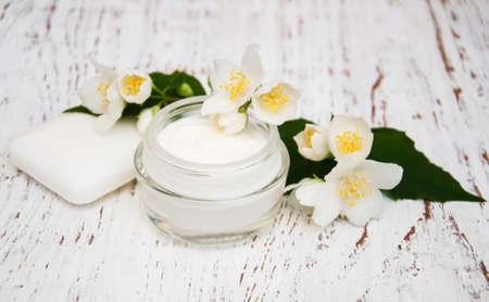 face and body cream moisturizers with jasmine flowers on white wooden background Archivio Fotografico
