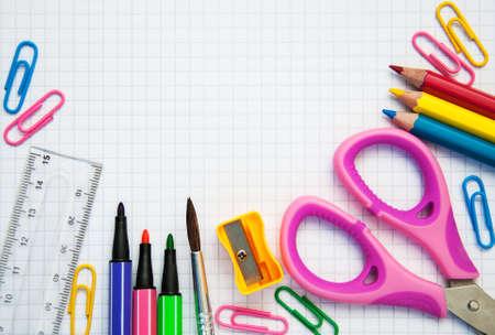 utiles escolares: Bloc de notas con material escolar sobre un fondo de madera