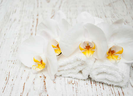 white orchids: White orchids and towels on a wooden background