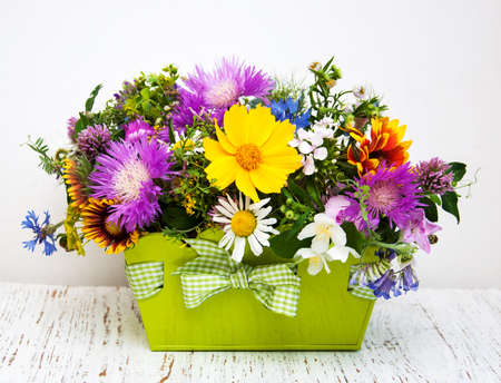 Wild flowers in a metal pot on  old wooden background Stock Photo
