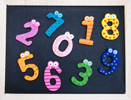 arabic numeral: School Blackboard with funny numbers on a wooden table Stock Photo