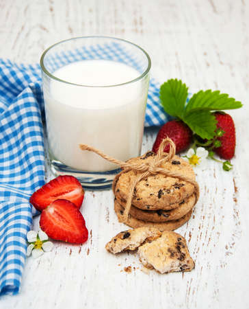 milk and cookies: Milk, cookies and strawberries on a wooden background Stock Photo