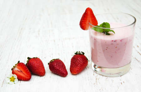 strawberries: Strawberry yogurt with fresh strawberries on a wooden background Stock Photo