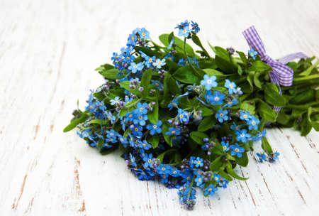 ramo de flores: Forget-me-no tienen las flores con la cinta en un fondo de madera