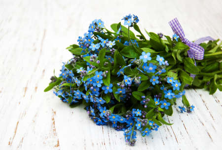 bouquet of flowers: Forget-me-nots flowers with ribbon on a wooden background