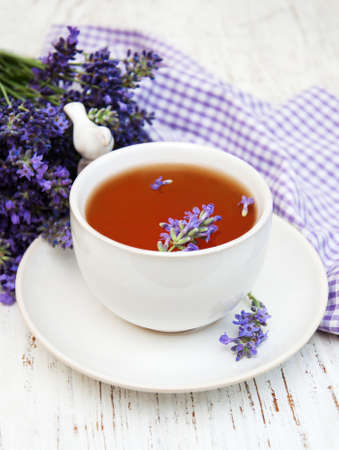 stimulating: Cup of tea and lavender flowers on a old wooden background
