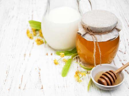 Linden honey and milk on a old wooden background Banque d'images
