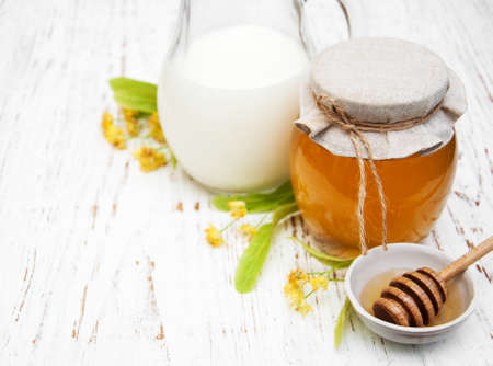 Linden honey and milk on a old wooden background Archivio Fotografico