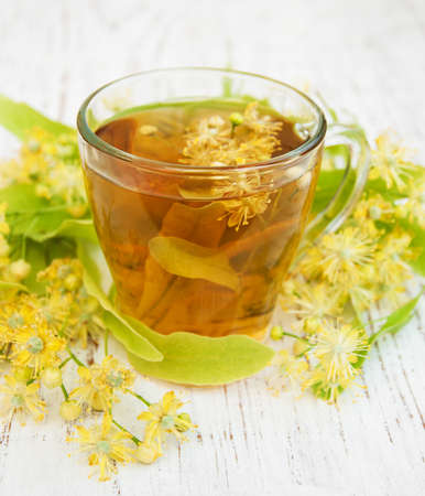 green yellow: Cup of herbal tea with linden flowers on a old wooden background