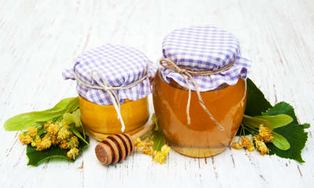 linden flowers: Jars with honey and linden flowers on a wooden background