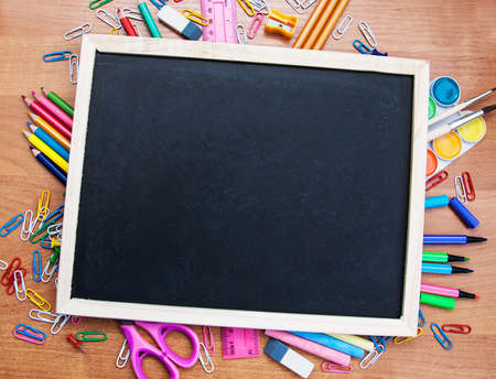 school supplies and blackboard on a wooden background