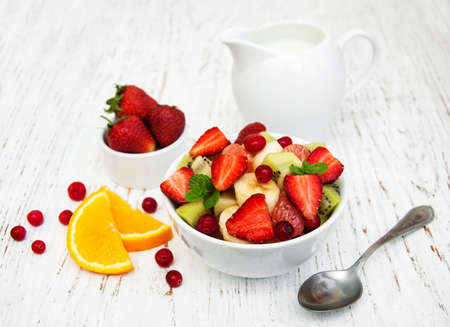 fruit: Salad with fresh fruits on a old wooden background