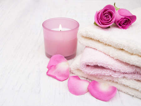 cotton flower: Bath towels with pink roses on a old wooden background Stock Photo