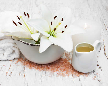 natural therapy: White lily, towels and sea salt on a old wooden background Stock Photo