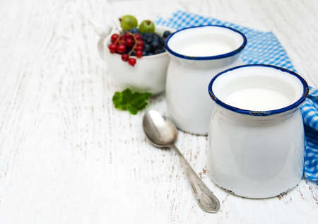 natural products: Homemade yogurt and fresh berries on a wooden background
