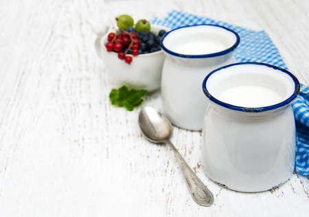 frescura: yogurt casero y bayas frescas en un fondo de madera