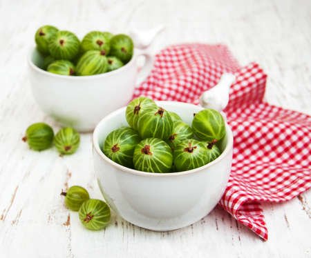 pulpy: cups with gooseberries  on a old wooden background Stock Photo
