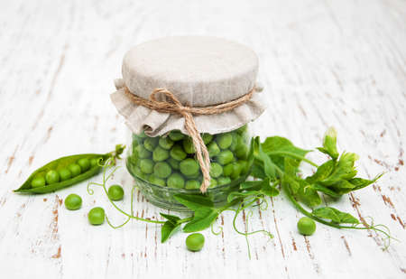 sweet sugar snap: Jar with fresh peas on a old wooden background Stock Photo
