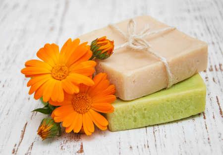 jabon: flores de caléndula y jabón de baño hecho a mano sobre un fondo de madera Foto de archivo