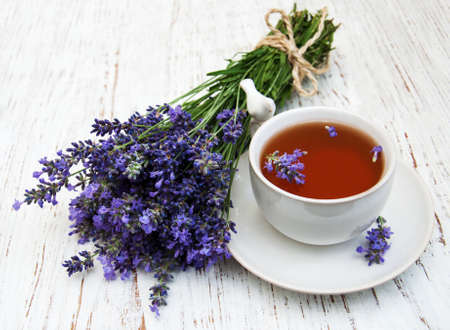 Cup of tea and lavender flowers on a old wooden background