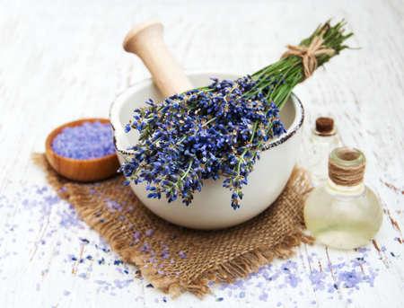 espliego: aceite de lavanda con sal de baño y lavanda fresca sobre un fondo de madera vieja