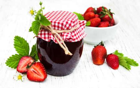 fresa: Mermelada de fresa y fresas frescas en un fondo de madera