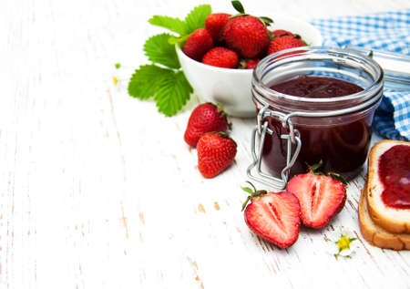 strawberries: Strawberry jam and fresh strawberries on a wooden background