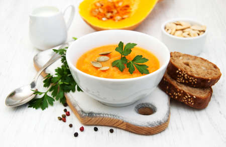 pumpkin soup: Bowl with Pumpkin soup on a old wooden background