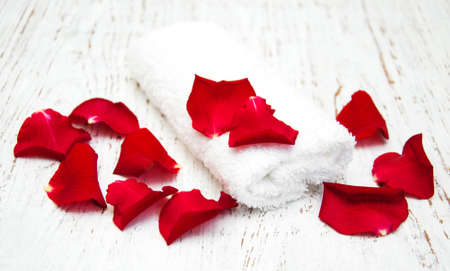 rose petals: Massage towels and red roses petals on a wooden background Stock Photo
