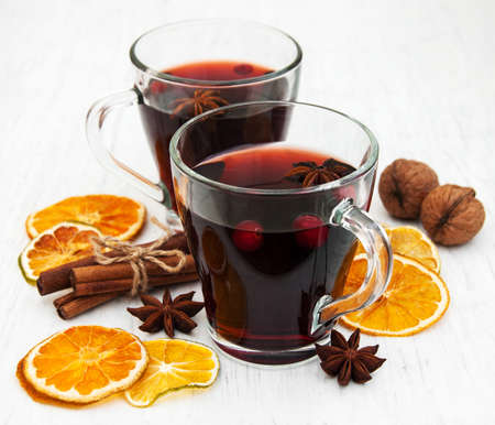 Glasses of mulled wine with spices on a old wooden background