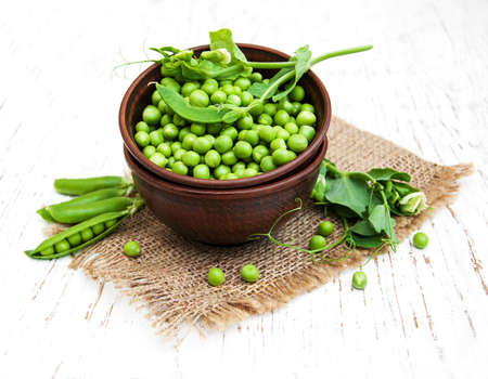 Bowl with fresh peas on a wooden background Stock Photo