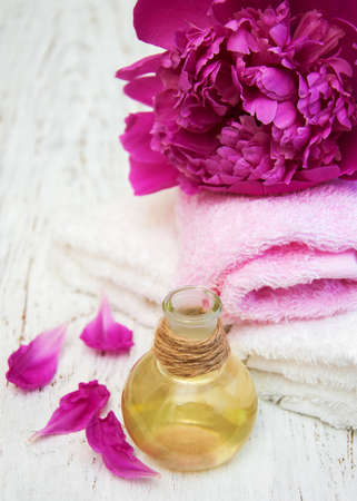 natural therapy: Peony flowers, massage oils  and towels on a wooden background